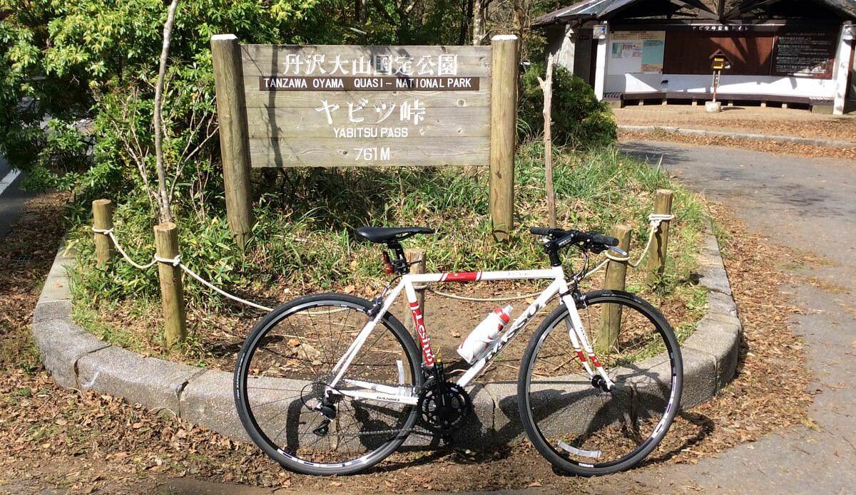 ヤビツ峠の看板前でクロスバイクと記念撮影した画像